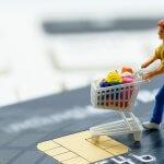 miniature figure of a man pushing a shopping cart