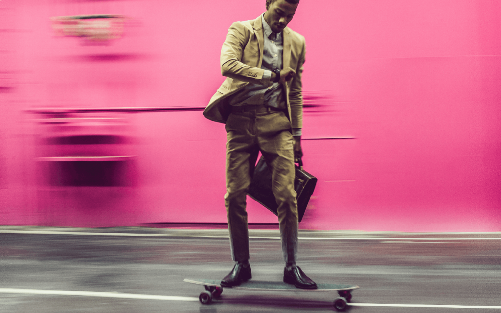 Picture of a man in a suit riding a longboard