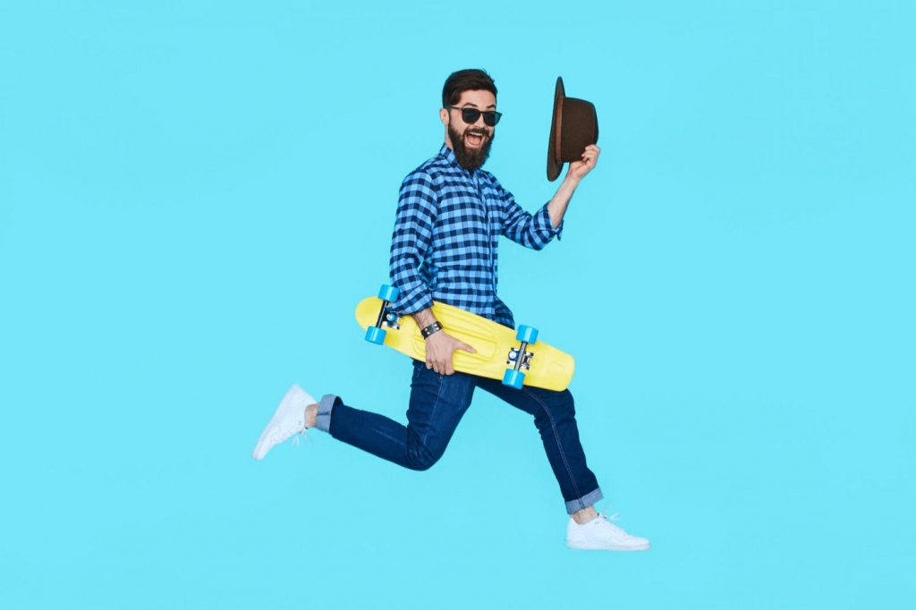 Picture of a guy with a skateboard and a hat jumping in the air